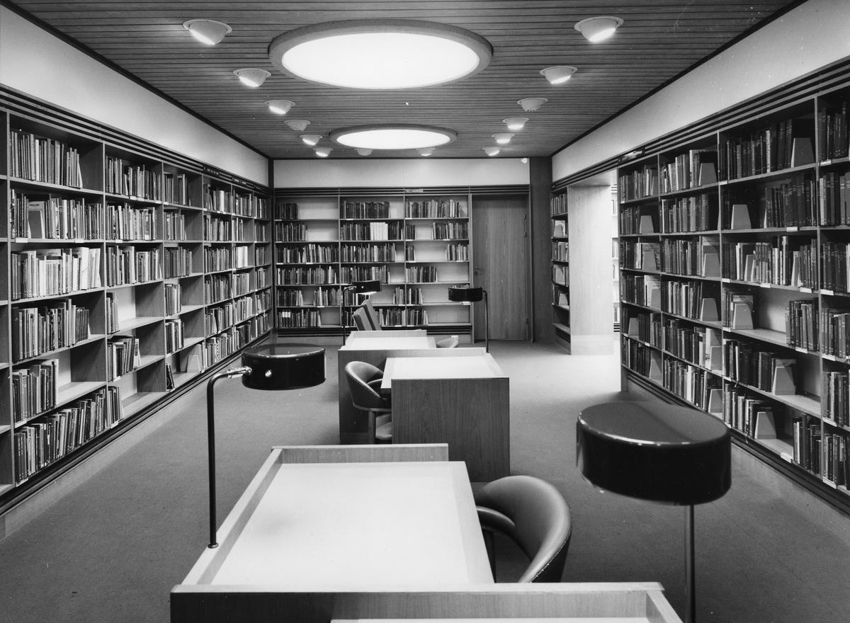 Arboga Stadsbibliotek, interiör. Facksalen, på markplan. Bokhyllor med böcker från golv till tak. Läsbord, med fåtöljer, i mitten av rummet. Dörren, på kortväggen, leder till personalens arbetsrum. Portalen, till höger, leder till stora bibliotekshallen.