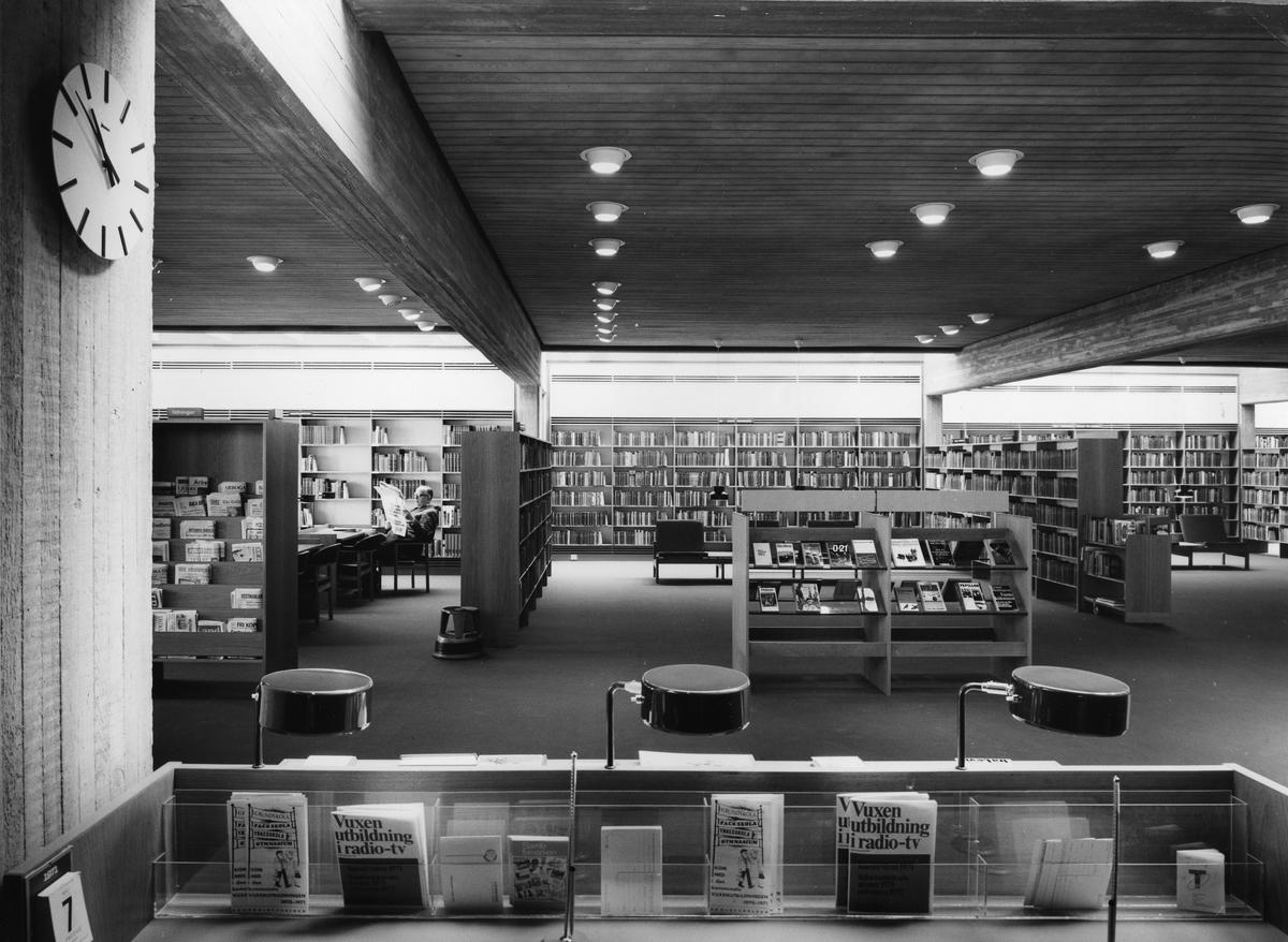 Arboga Stadsbibliotek, interiör. Fotografen har entrén bakom ryggen. Bilden är tagen ut i stora bokhallen. Bokhyllor med böcker, från golv till tak.