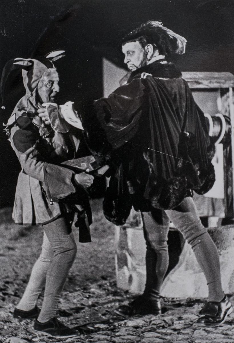 """Rune Lindström spelar rollen som Engelbrekt Gertsson (till höger). Narren är oidentifierad. """"Giv oss fred"""", även kallat """"Arbogaspelet"""", är ett teaterstycke skrivet av Rune Lindström 1961. Handlingen, som är inspirerad av Arbogas klosterhistoria, är förlagt till början av 1500-talet. Uruppförandet skedde den 11 augusti 1962 och Rune Lindström spelade Engelbrekt Gertsson. Lions Club i Arboga stod för arrangemanget. Föreställningarna regnade bort och det blev ett stort ekonomiskt bakslag för föreningen. Spelet har framförts igen; 1987, 1988, 2012 och 2015 av medlemmar i """"Bygdespelets Vänner""""."""