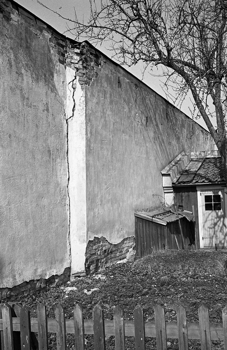 Exteriör. Trasig fasad bakom staketet. Miljö.  Fotografens anteckning: Dokumentation av fastigheter i kvarteren söder och norr om ån. Bilder och beskrivningar finns på Arboga museum.