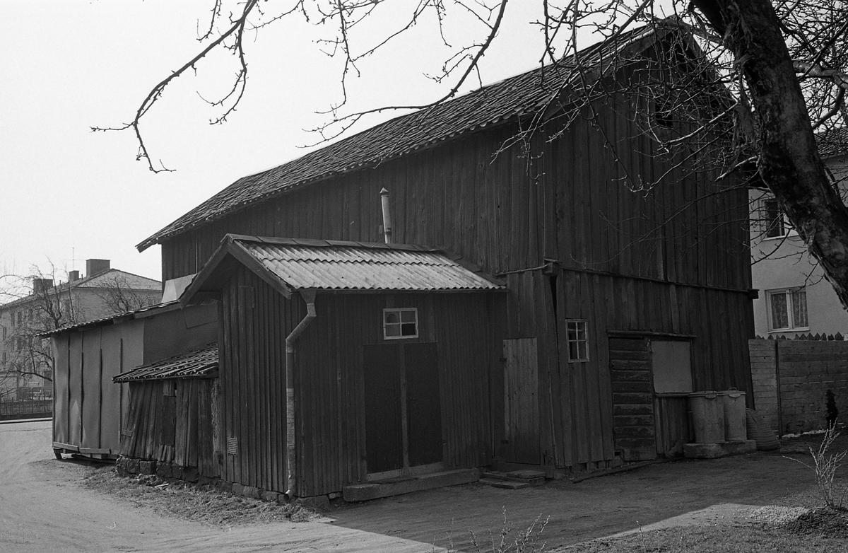 Exteriör. Uthus/förråd. Två soptunnor står utanför. Intill uthuset ses två nyare flerfamiljshus. Fotografens anteckning: Dokumentation av fastigheter i kvarteren söder och norr om ån. Bilder och beskrivningar finns på Arboga museum.