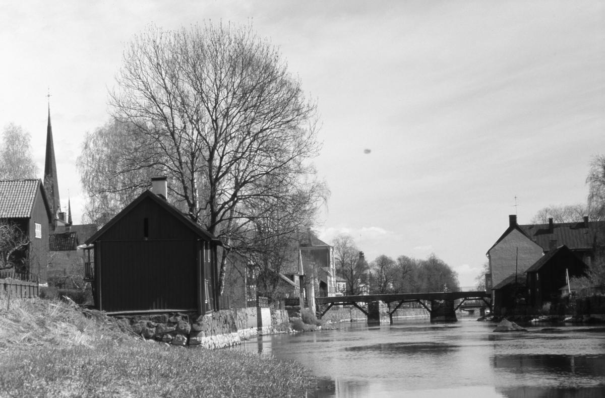Vy. Ågårdar norr och söder om Arbogaån. Tornet på Heliga Trefaldighetskyrkan till vänster. Kapellbron mitt i bild.