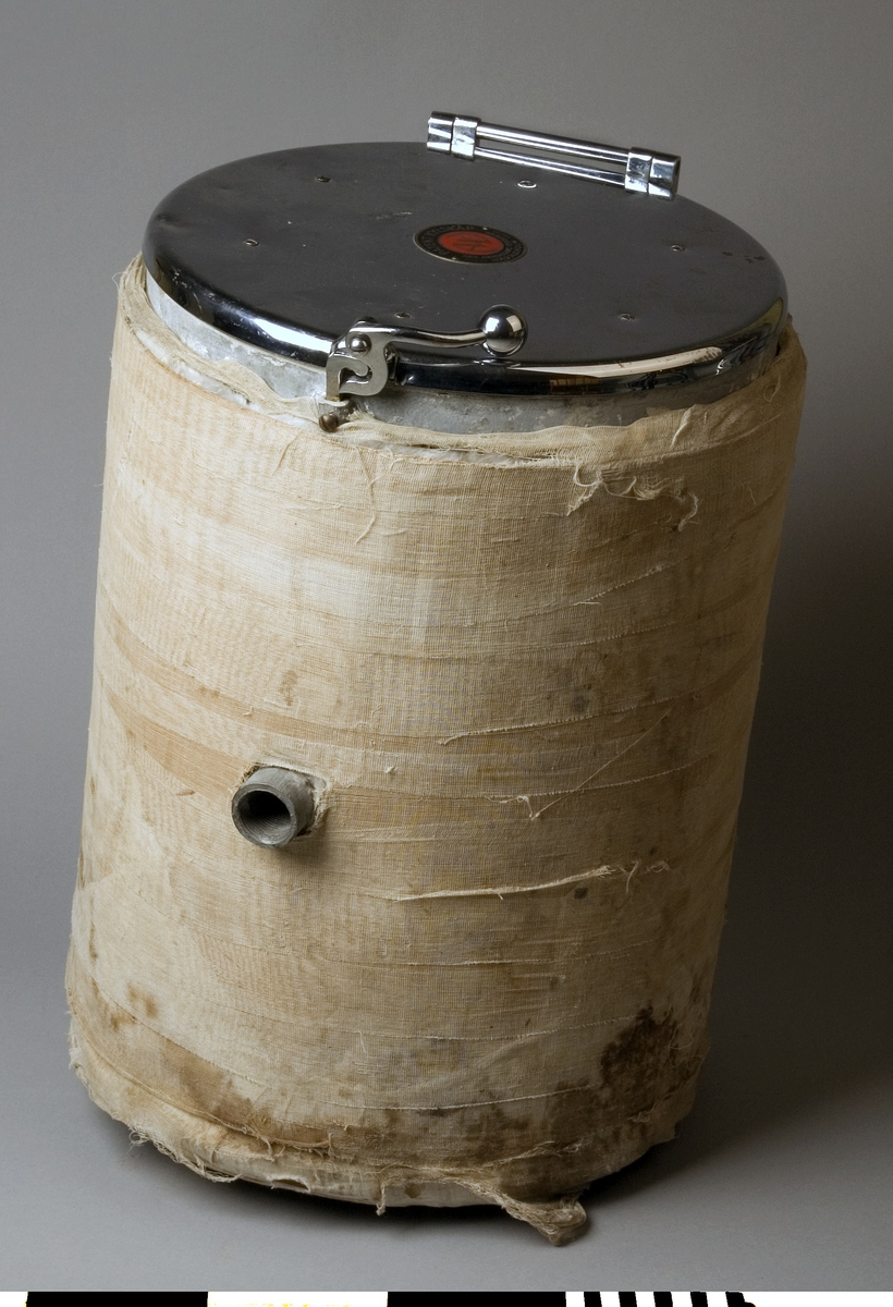 """Kylskåp av stål och textil. """"Patent kylskåp"""" för kallvattenanslutning. Text på locket: PATENT KYLSKÅP, ARV. ANDERSSONS VERKSTÄDER, HÄSSLEHOLM. På lockets insida: Skötselanvisningar.  Det runda kylskåpet var avsett att monteras in i köksinredningen. Kylskåpet anslöts till kallvattenledningen och förbrukningsvattnet cirkulerade i det dubbelmantlade skåpet innan vattnet användes i köksarbetet.  Funktion: Håller maten vid kall temperatur"""