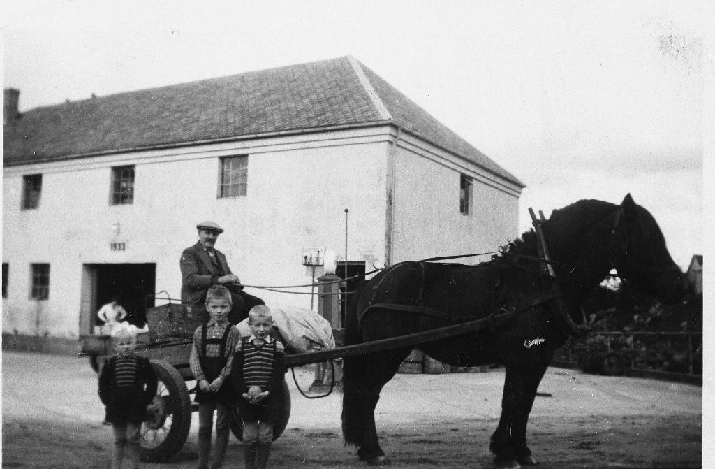 Severin Skårland med hest og mjølkekjerre framfor meieriet på Undheim i slutten av 1940 åra. Ein del bønder frå same krinsen ordna seg slik at dei frakta mjølka kvar sin gong.