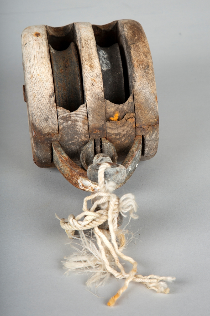 Liten, dobbel blokk. Tilstand ok. Innretning brukt for å løfte for eksempel fiskekasser.   Blokka og skivene er laget av tre og metall. Mangler krok, men har en stump nylontau festet i ringen, der kroken trolig har vært.