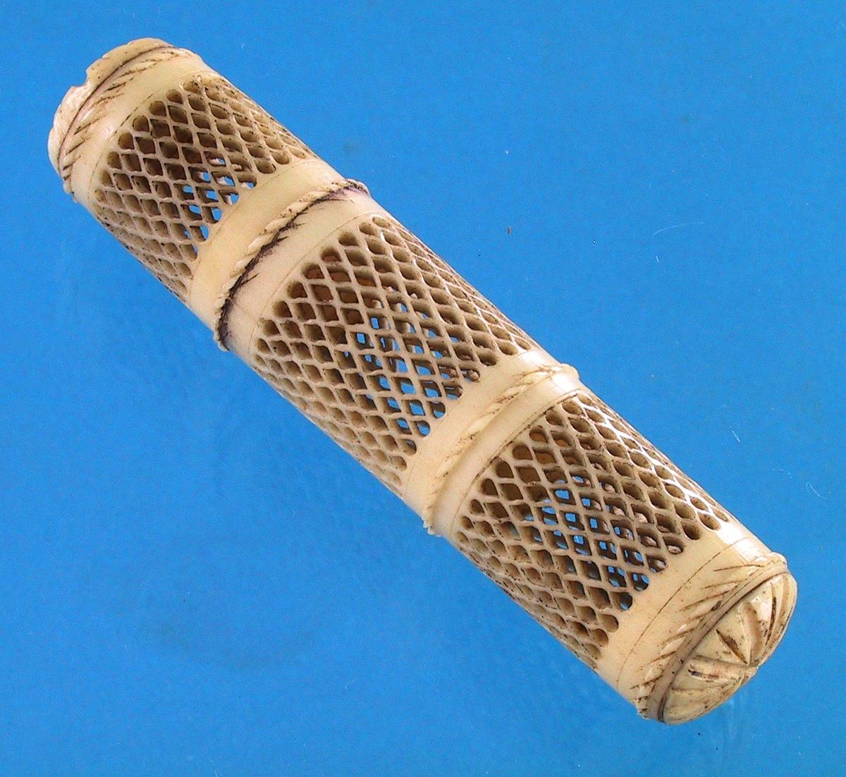 Lusefelle (loppefelle). Ben, utskåret. Sylinder med tre brede felt av åpne ruter, mellom disse en smal snodd bord, i endene svakt hvelvede rosetter. Den ene tredjedel kan skrus av.