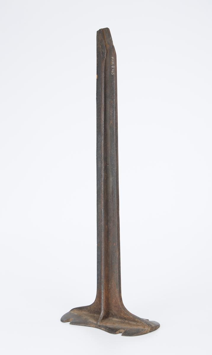 Jern stativ med skoform på toppen (FHM.0874). Opplysninger kan faaes hos skomaker O. Pedersen i Droebak
