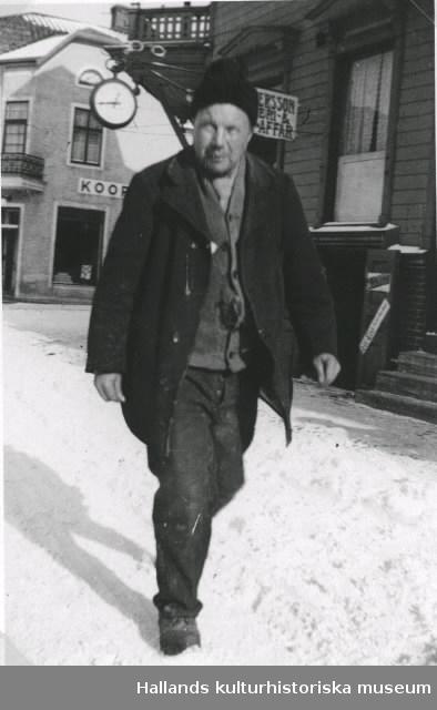 """""""Balla-Kalle"""" utanför den s k Millbergska fastigheten, kv Hantverkaren 1, med Norrmans Uraffär på hörnan. I bakgrunden syns Kooperativa, kv Nålmakaren någon gång på 1930- eller 1940-talet."""