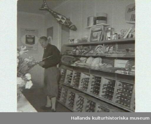 """Affärsinteriör med staplade drickabackar i trä och en man i """"äppelknyckarbyxor"""". """"Kooperativa öppnar ny affär på Getterön"""". Artikel i samband med bilden publicerad i Varbergs Tidning 1955-06-15."""