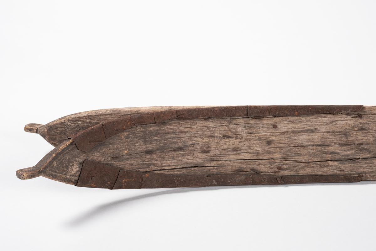 SKi B er spikret o skrudd mot undersiden av ski A.  Skien har litt innsving på midten. Bak er den rett og foran er tuppen spiss og krummet oppover, med en tapp ytterst. Den er jernbeslått foran, nesten fram til tuppen (dvs. at undersiden er dekket med jern, som er brettet oppover kanten og spikret og skrudd fast). På midten er det spor og rester etter spiker, samt at det sitter en skrue der. I sidene ser man at det er laget hull tvers gjennom skiene, som er tettet igjen med en trebit. Undersiden av skiene har tre renner.