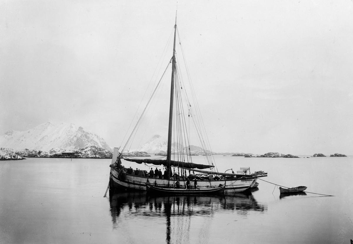 Motivet viser en nordlandsjekt for anker i kystlandskap. Det er snø på fjellene og svabergene. Syv mann ombord på jekten, og tre mann i lettbåt som ligger fortøyet langs skutesiden.