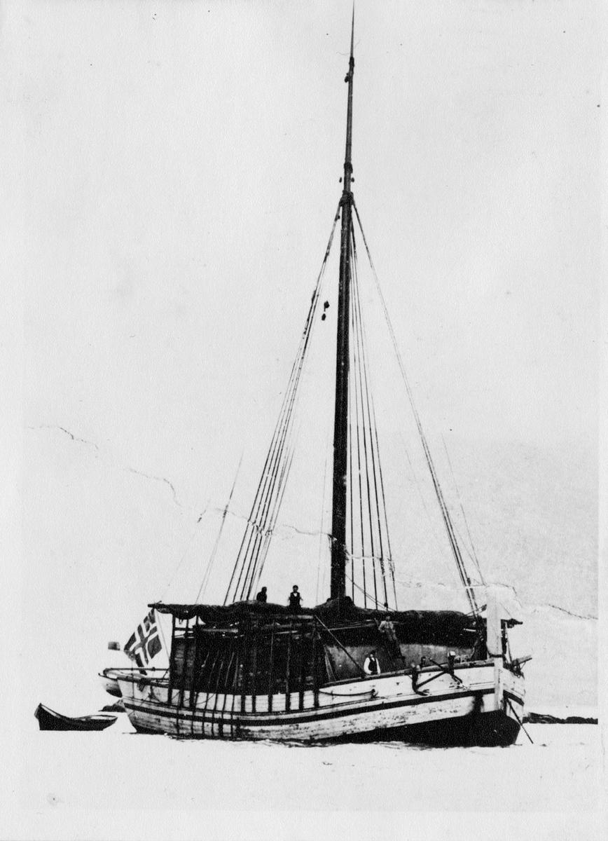 Motivet viser nordlandsjekten LYDIA (seinere M/S MALSTRØMMEN) lastet med tørrfisk. Fire menn ombord og norsk flagg i akter.