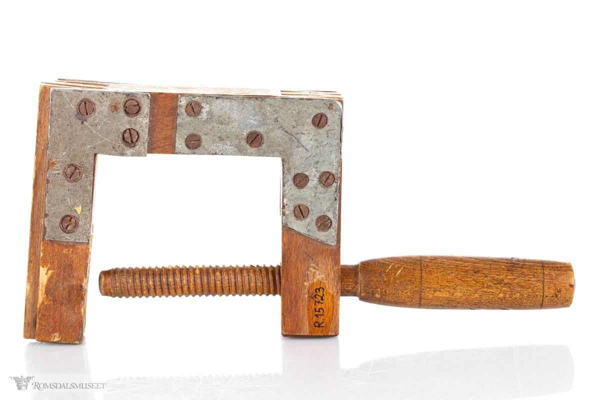 Liten, notet tvinge av tre som er forsterkt med kraftige metallbeslag og skruer. Dreid trearm med gjenger.