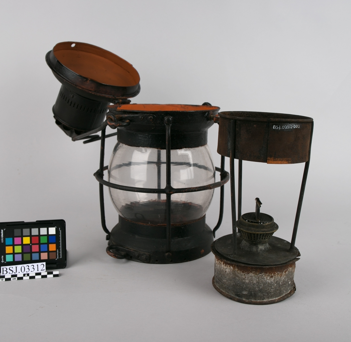 Kulelanterne med parafinbrenner/oljebrenner. Rund hank for opphenging og åpning på topp for å komme til brenneren. Klart lampeglass med beskyttelsesgitter.