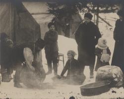 Människor i olika åldrar har samlats kring en eld i snön. Ma