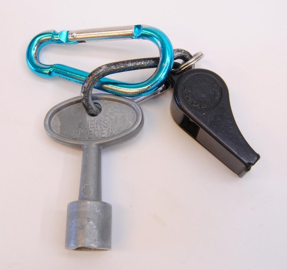 """Godsvagnsnyckel. På ena sidan står det """"AVÉNS SWEDEN"""" och på andra sidan """"PG 312"""". Nyckeln har en invändig trekant."""