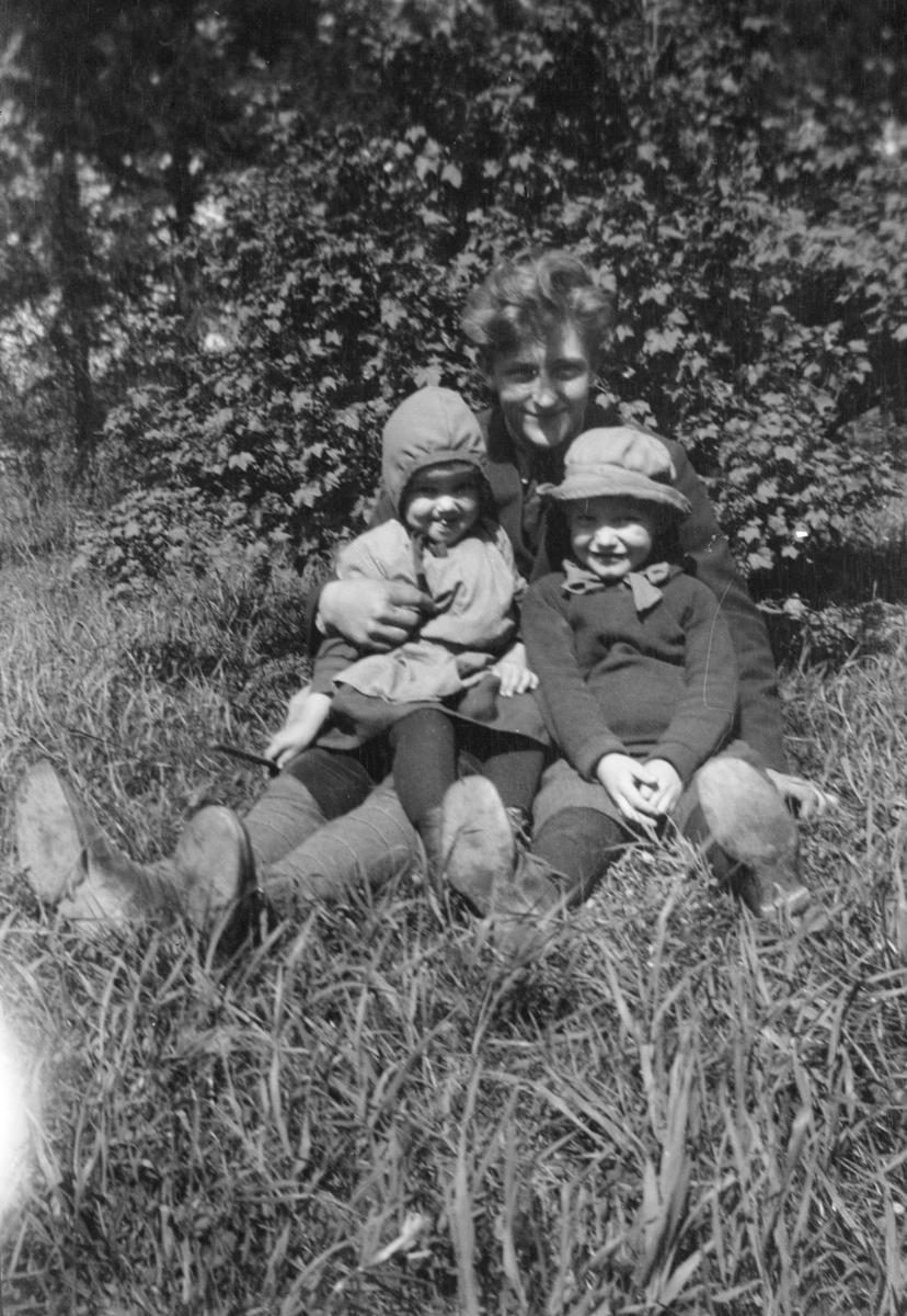 Kvinne med to barn, sittende i gresset
