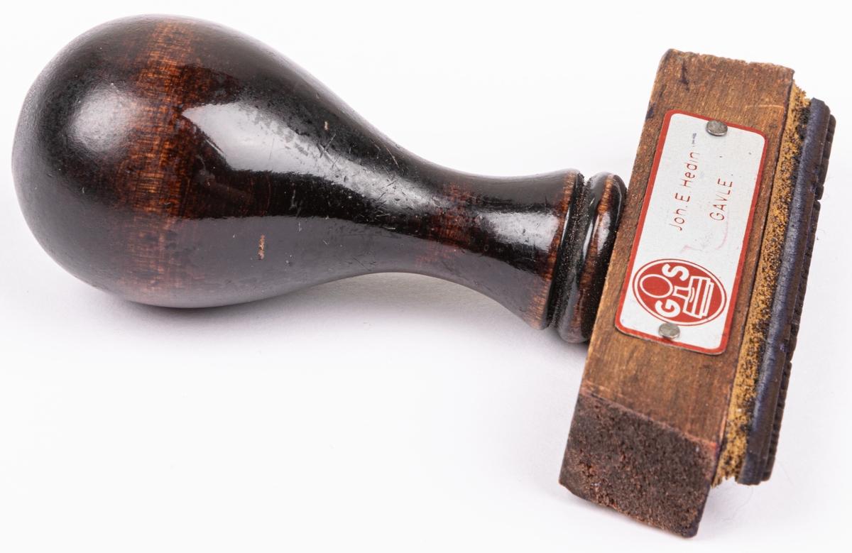 """Acckatalog. Gummistämpel med brunt droppformat handtag. Nit på ena sidan. Guldfärgd etikett med röd bård och text. Stämpeltext;"""" Direktionen för stiftelsen Sjömanshuset i Gävle"""".  Lappkort.  Gummistämpel med brunt droppformat trähandtag. Pånitad silverfärgad metallskylt med röd bård och text: """"Joh. E. Hedin Gävle"""" och """"GS"""". Stämpeltext; """" Direktionen för Stiftelsen Sjömanshuset i Gävle"""". Gåva av sjömansförmedlingen i Gävle."""