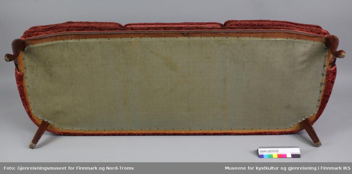 Sofaen er trukket med rød fløyel med fremhevet floralt ornamentmønster. Sofaen har plass til tre personer. Kanten på sofaryggen er av lakkert tre, er buet og går over i armlener med sider som buer utover. Ramma til sittedelen har et ornamentmønster innskåret foran på midten og  går over i løveføtter foran og firkantede føtter bak. Polstringa til sitteflata er dekket med tynn lerretstoff både under og over. Stoffet er spikret fast i ramma. På denne polstringa ligger det tre separate sitteputer med fjæring og de kan tas av. På ryggstøtta er polstringa inndelt i tre seksjoner.