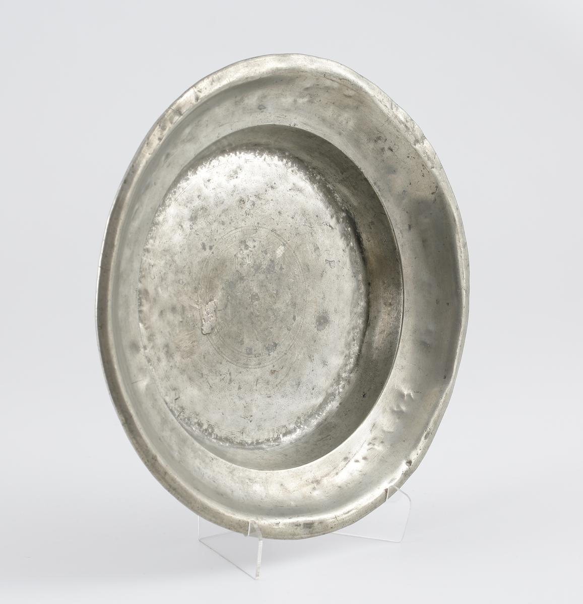 """Fat av tenn.  Djupt fat med uppsvängd bräm. Dekorerat i spegeln med fyra ringar och streck. Ägarinitialer på kanten: """"IPD"""".  Stämplar inslagna i spegeln, men nästan helt bortnötta."""