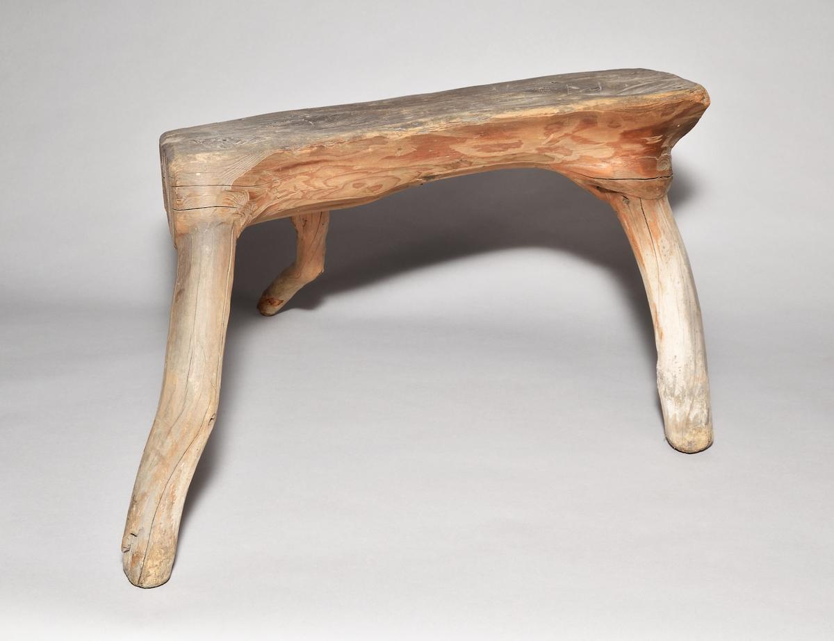 Pall av trä. Gjord i ett stycke, självvuxet, där de tre benen utgörs av  grenarna. Rektangulär sits.