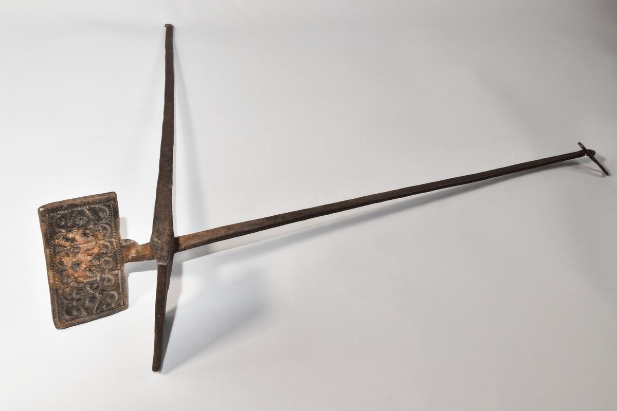 Rånjärn av järn, långa skänklar som hålls ihop med ovalt järnlås. Rektangulär rånform ornerad inuti med stjärnmönster.