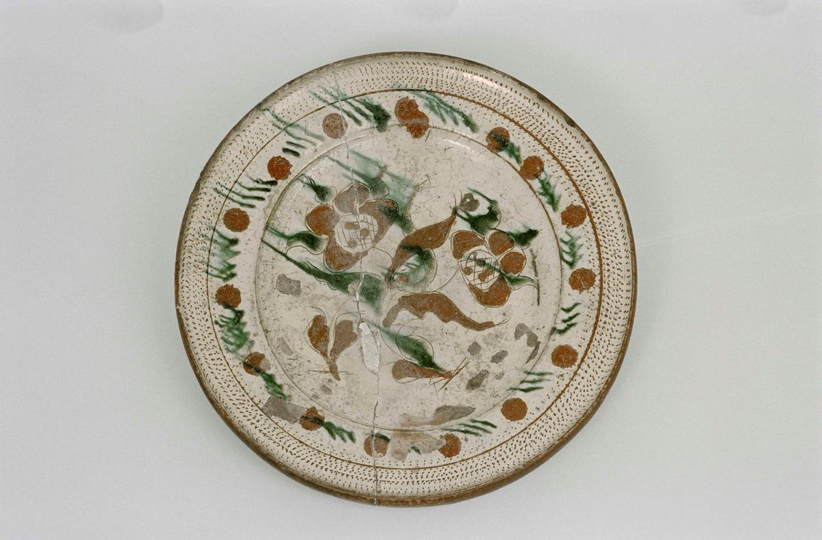 Fat av lergods, lätt skålat, blyglaserat invändigt, engoberat i gulvitt med tulpandekor i brunt och grönt. Utmed kanten hemrad prickdekor. Utvändigt oglaserad. Glasyrbortfall, genomgående spricka.