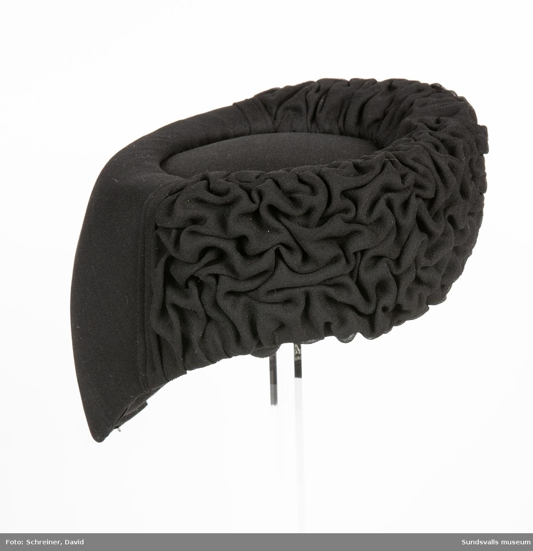 En svart hatt med neddraget nackparti, stoppad slät kullplatta och framkant i murkelstrukur.