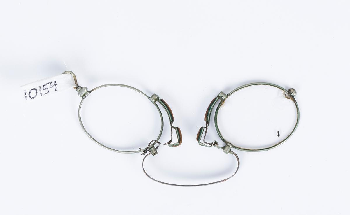 Lorgnett, to ovale seglass med klemmeinnretning til nesen. Mangler ett glass, det andre er noe knust. Hjemmereparert.