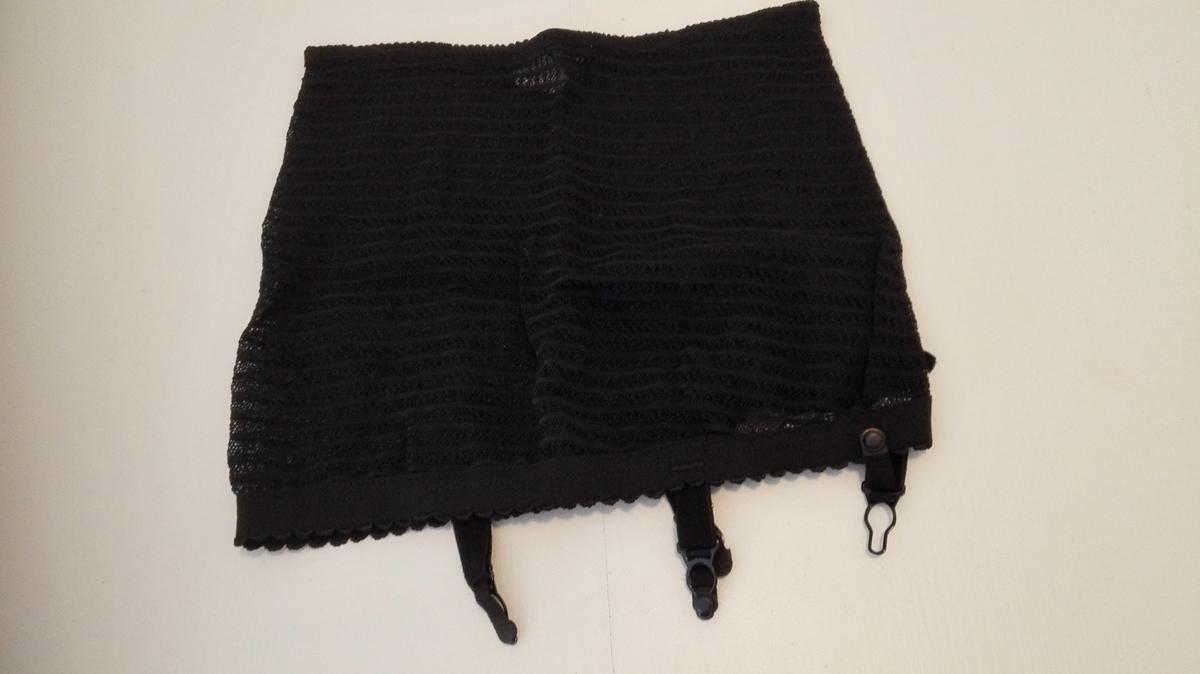 Elastikk bak og på hoftene. 15 cm breitt forstykke/midparti av uelastisk stoff med blonder. Pynta med sløyfe. Stropper framme og bak.
