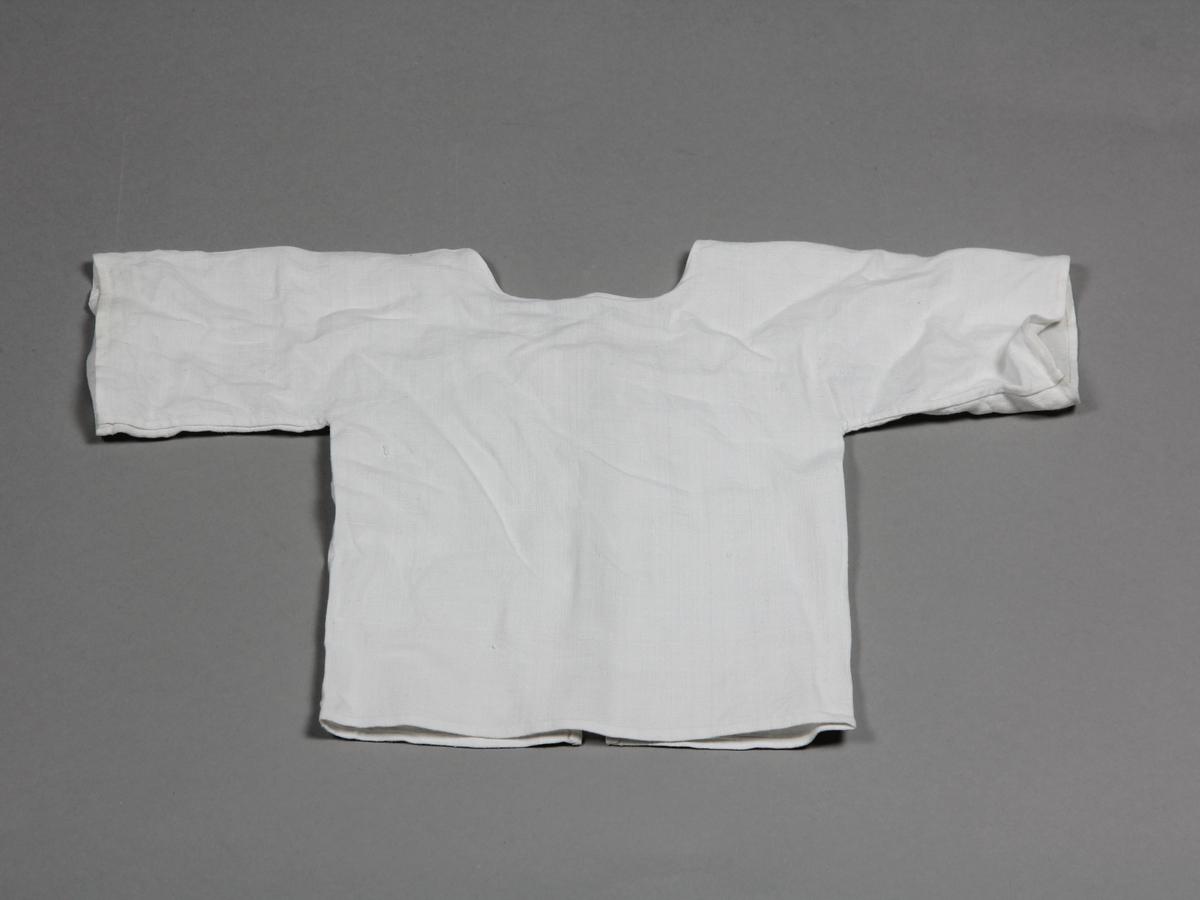 Skjorta av tunt vitt linne, för spädbarn. Knyts i ryggen med två par band.