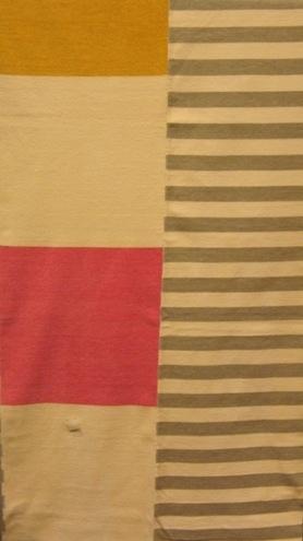 Ett mjukt och kraftigt överkast i kypert. Vävt med bomullsgarn i varpen och velourgarn i inslaget. Överkastet är vävt i tre delar som är hopsydda. Sidstyckena är grå och vitrandiga, mitten stycket är blå, vit, gul, rosa i kvadratiska rutor.  Överkastet är märkt med R31:1 på ett vitt bomullsband. En fyrkantig vit klisterlapp med texten TRIO är fastklistrad i ena änden.  Överkast med modellnamn Trio är formgivet av Ann-Mari Nilsson och tillverkat av Länshemslöjden Skaraborg. Det finns med  på sidan 72-73 i vävboken Inredningsvävar av Ann-Mari Nilsson i samarbete med Länshemslöjden Skaraborg från 1987, ICA Bokförlag. Se även inv.nr. 0001-0030,0032-0040.