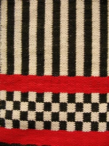 En kraftig och stadig trasmatta vävd i två stycken, ihopsydd på mitten. Mattan är vävd i inslagsförstärkt tuskaft, den är rutig och randig både vågrätt och lodrätt i olika partier. Färgerna är svart,vit röd, gul och blå. Inslaget består av enfärgade bomullstrasor och det är sextrådig oblekt bomullsmattvarp.  Mattan är märkt med R38:1 på ett vitt bomullsband.  Matta med modellnamn Hanna är formgivet av Ann-Mari Nilsson och tillverkat av Länshemslöjden Skaraborg. Det finns med  på sidan 90-91 i vävboken Inredningsvävar av Ann-Mari Nilsson i samarbete med Länshemslöjden Skaraborg från 1987, ICA Bokförlag. Se även inv.nr. 0001-0037,0039-0040.
