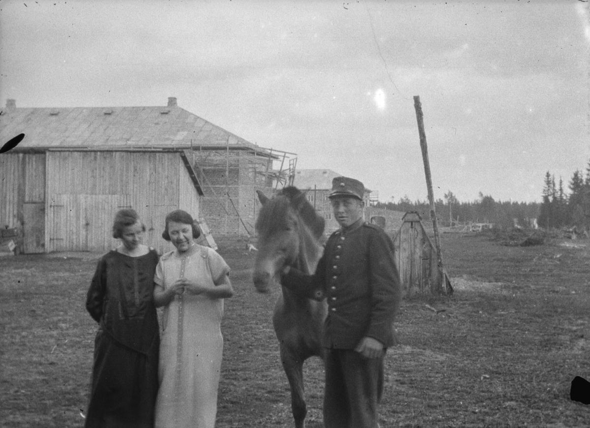 Soldat med en hest. To unge damer. Brønnhus og store bygninger i bakgrunnene