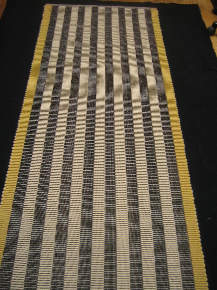 """Matta vävd i rips med ullgarn i varp och tjockare ullgarn i  inslag. Mattan består av 17 ränder de 15 i mitten är svarta och vita och kanterna har lila garn på ena sidan och gult garn på andra sidan. Det är en 3 cm bred fåll i avsluten. Mattan är monterad på en träribba med texten """"Repslagaren II, Ann-Mari Nilsson""""."""