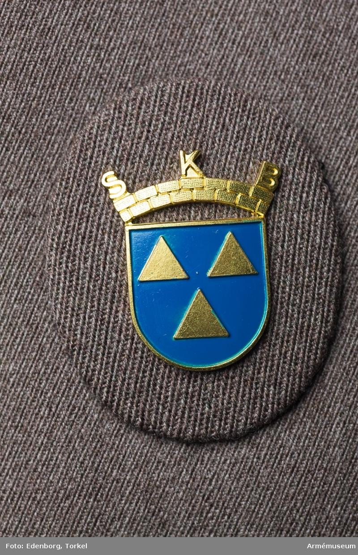 Grupp C I. Ur tjänstedräkt m/1942 för kvinnliga bilkåren. Består av jacka,  kjol, fältbyxor, fältmössa, barett, två blusar, två slipsar, manschettknappar, handskar. Jackan har tecken för genomgångna kurser på axelklaffarna: röd =  sjukvård, grön = orientering, fot, bil, mörkblå = materielvård,  vit = lastbil, ljusblå= stora motorkursen. Sveriges första kvinnliga bilkår bildades i Göteborg 1939. 1942  bildades det övergripande organet Sveriges kvinnliga bilkårers  riksförbund, SKBR, som idag organiserar 125 bilkårer runtom i  landet. 1997-01-31 /GO. Uniformen är av den typ som användes i landsorten. Stockholms bilkårister hade en mera blågrå uniform med längre jacka och påsydda fickor.