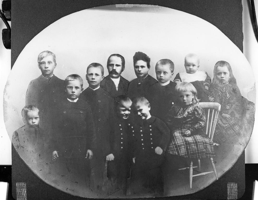 Biletet er laga av ein omreisande fotograf ca 1930. Familiebilete samansett av 4 forskjellige foto og viser foreldre med 10 born. Foreldra er Isak Kristiansen Time (1863 - 1949) og Oline Nilsine Eriksdtr. Frette frå Etne (1875 - 1956). Dei gifta seg i 1897 og biletet av dei er frå brurebiletet, sløret er retusjert bort. Dei 4 gutane til venstre er : Isak J. Time (1907 - 1990), Olav Time (1909 - 1991), Bjarne Time (1913 - 1997, Stein Time (1915 - 1990). Originalen fotografert ca 1915. Framme i midten tvillingane Holger Time (1918 - 1989) og Harald Time (1918 - 1998). Originalen fotografert ca 1923. Dei 4 borna til høgre er : Tora Marie Time (1898 - 1974), Kristian Time (1900 - 1977), Margrethe Time (1902 - 1990) og Einar Time (1904 - 1996). Originalen fotografert ca 1905.