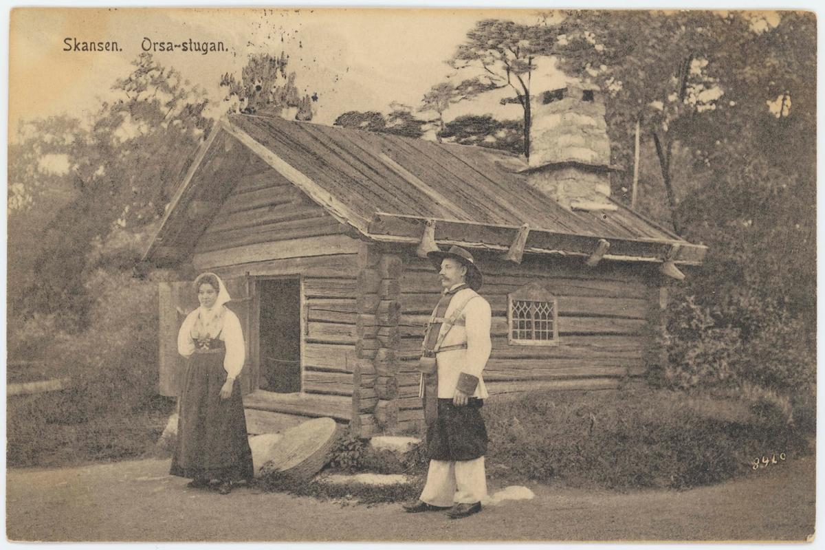 """Vykort med motiv från Skansen. """"Orsa-stugan"""". Man och kvinna i folkdräkt utanför stugan."""
