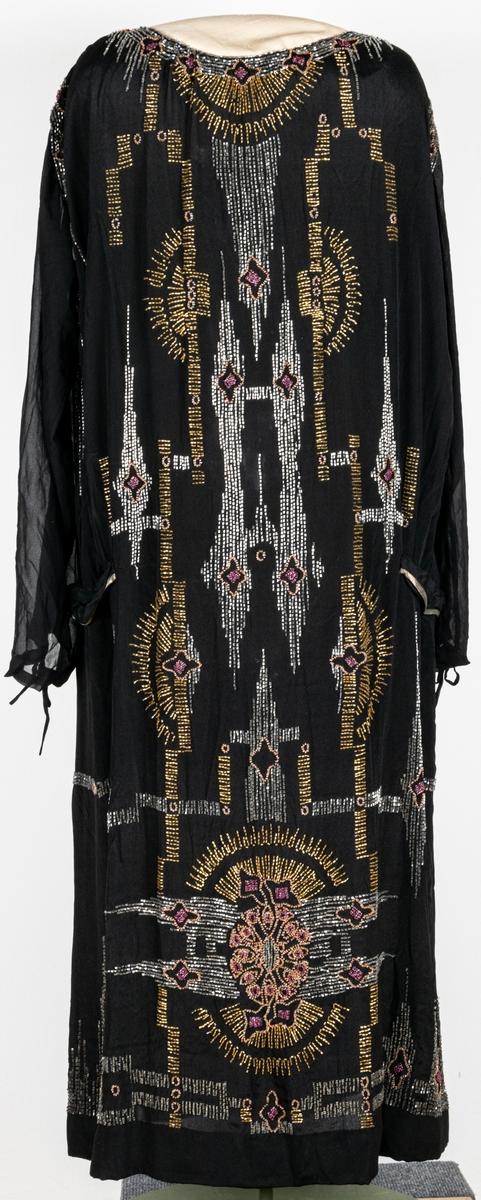 Svart klänning från 1920-talet. Rikligt pärlbroderad i lodräta mönster. Pärlor i silver, guld och cerise. Lång ärm med knyt i muddarna.