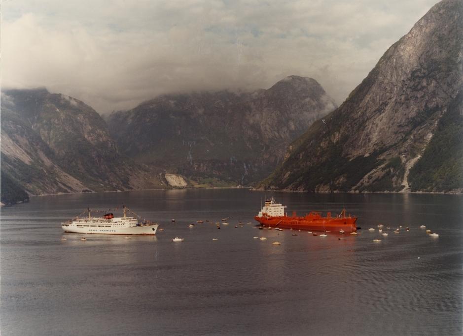 Motivet viser M/T MAURANGER (bygget i 1981 for Westfal-Larsen) og M/S ENGLAND fra DFDS Seaways, samt en rekke mindre fritidsbåter, i Maurangerfjorden.