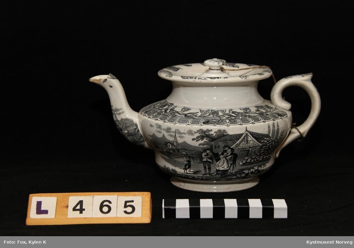 Tekanne brukt til sjenking av te eller varmt vann. Denne tekanne har en tut og lokk alt laget av porselen. Motiv av Familie med barn, hest, hund, hus, og kirke i bakgrunn.