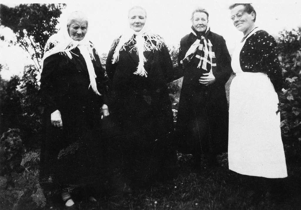 Gamle kvinner med kvite finplagg laga av tynn ull med silkefrynser. Frå v. : Jorina Egeland (? - 1952). Ho dreiv gard på Lye (Rudlå) - nåværande eigar (1990) er Sverre Risa. Maria Bø ( ? - d. 1945), søster til Oskar Fosse (Bøen), Pauline Time (Moldhaug), Olava Auglænd (1889 - 1969) g. m. Albert Auglend.  Dei tre eldre konene budde på Bryneheimen og var på kaffibesøk hos Olava. Biletet er teke i krigsåra 1940 - 1945.