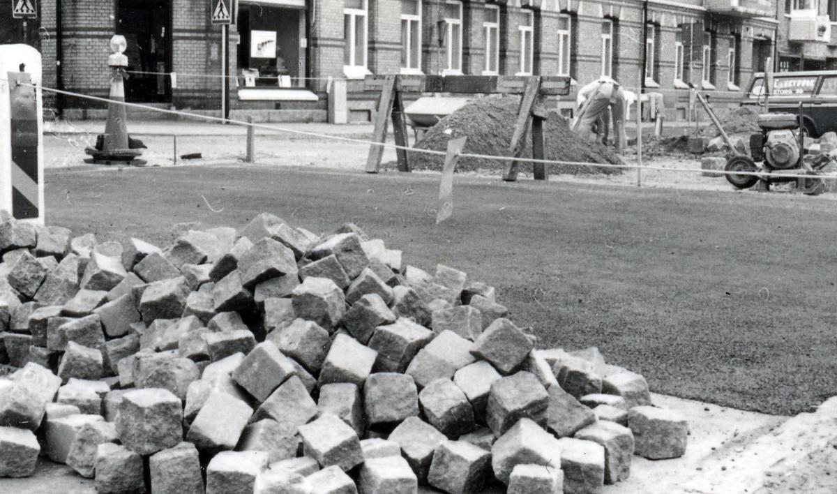Fortsättning av dokumentationen av järnvägsinfarten. Korsningen Norra vägen -Badhusgatan. Mittpartiet förhöjt och hastigheten begränsad till 30 km i tim. Stensättningsarbeten.