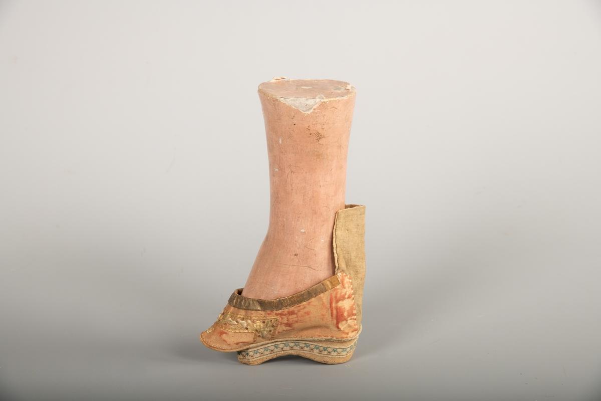 a) Fot i   gips  med malt   papp  utenpå. Sko:   silke og   lin. Hælen er sterkt forskjøvet, som en sokkel under skoen.  Tøffelen har en gyllen farge og et bredt   forgylt  bånd i overkant. Bunnfargen virker som om den opprinnelig har  vært sterkere og dypere rød.   Broderier  over tåen og langs kanten av hælen.