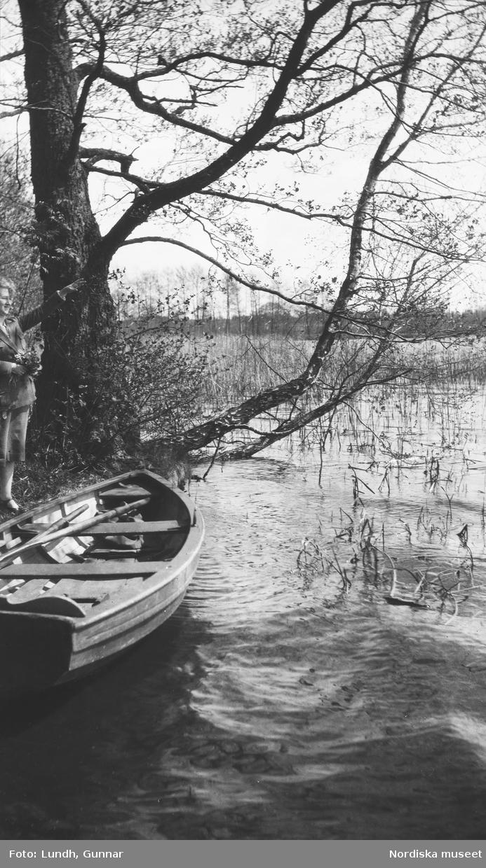 """Motiv: Utlandet, Rheinberg 109 - 113 ; En kvinna som håller blommor står vid en båt vid en strand, anteckningar på kontaktkarta 111 """"vitsippor i skog"""" 113 """"Reinberg""""."""