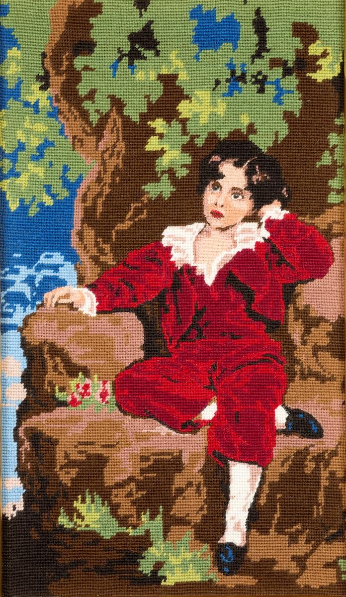 Rektangulært håndbrodert bilde. Motiv: Gutt i brun fløyelsdress sitter på en sten under et tre.Enkel gullramme
