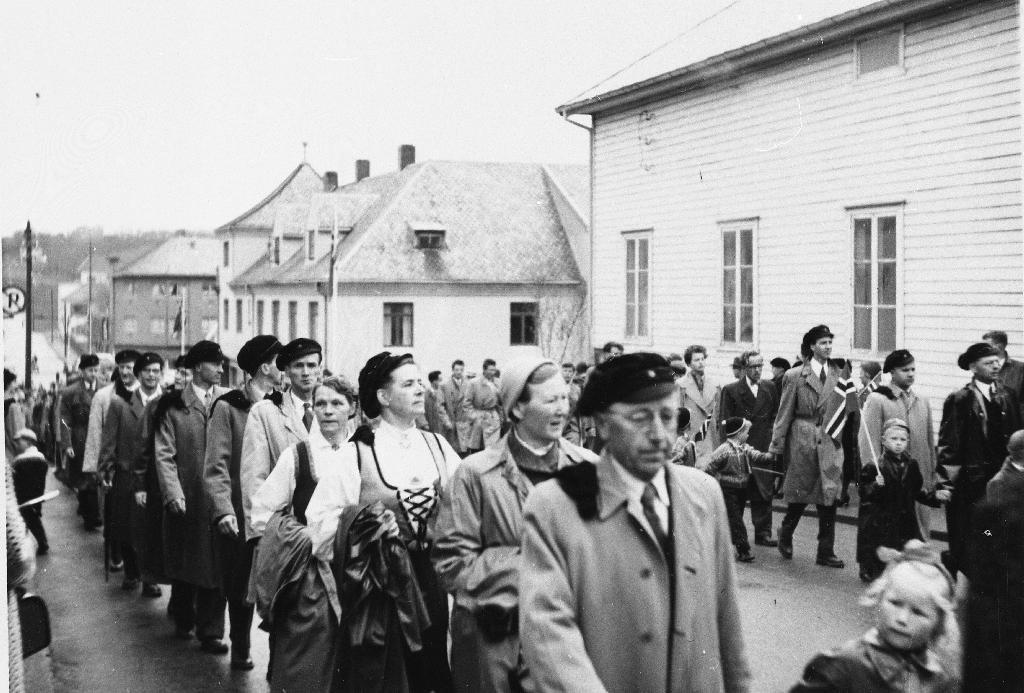 """Lærarar ved Bryne Gymnas saman med koner og barn i 17. mai tog i 1957. Bedehuset """"Saron"""" til høgre."""
