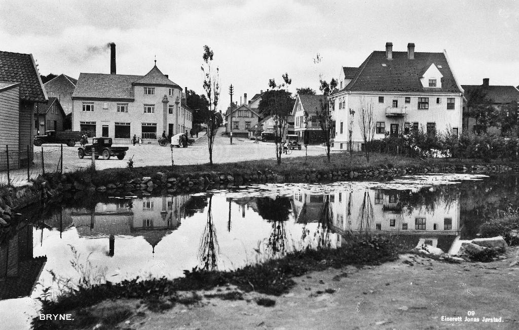Dammen og Torget på Bryne. Til v. Jæren Forbruksforening med pipa på Jæren Meieri bakanfor. Til høgre S. Tjemsland sitt hus bygt i 1920. Prospektkort.