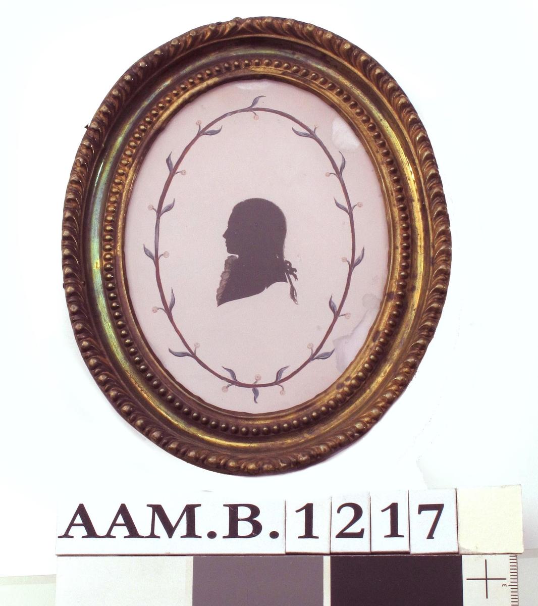 Liten silhouett  av v. vendt ung mann med hårpisk med sløyfe og kalvekryss, avskåret ved skuldrene.  Omgitt av en brun oval ring med blå blad og små gule blomster.