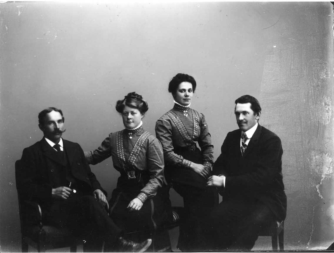 Gruppbild med två unga kvinnor sittande mellan två män. Kvinnorna är klädda på samma sätt med mörk kjol och rutig blus med prickiga band som löper från över axel snett ned mot naveln. Männen bär kostym och kravatt.